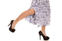 Vrouw in de hiel die van rokbenen omhoog in werking wordt gesteld royalty-vrije stock foto