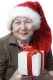 Vrouw in de hoed van de Kerstman met gift Stock Fotografie