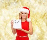 Vrouw in de hoed van de santahelper met het winkelen zakken Royalty-vrije Stock Afbeelding