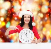 Vrouw in de hoed van de santahelper met klok die 12 tonen Royalty-vrije Stock Afbeelding