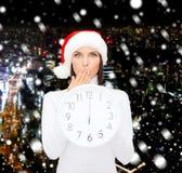 Vrouw in de hoed van de santahelper met klok die 12 tonen Stock Foto