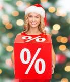 Vrouw in de hoed van de santahelper met rood verkoopteken Stock Foto