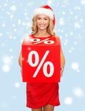 Vrouw in de hoed van de santahelper met rood verkoopteken Royalty-vrije Stock Foto