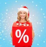 Vrouw in de hoed van de santahelper met rood verkoopteken Stock Afbeelding