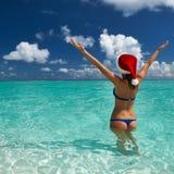 Vrouw in de hoed van santa bij strand royalty-vrije stock afbeeldingen