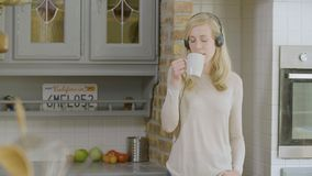 Vrouw in de keuken die aan muziek in haar hoofdtelefoons luisteren die koffie drinken stock video