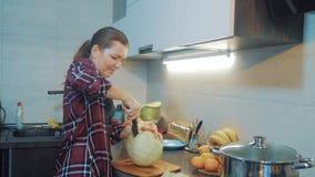 Vrouw in de keuken die een maaltijdconcept voorbereiden meisje in de kool van keukenbesnoeiingen met een mes kok vegetarisch voed stock videobeelden