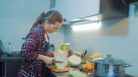 Vrouw in de keuken die een maaltijdconcept voorbereiden meisje in de kool van keukenbesnoeiingen met een mes kok vegetarisch voed stock footage