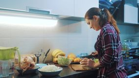 Vrouw in de keuken die levensstijl voorbereiden een maaltijdconcept meisje in de kool van keukenbesnoeiingen met een mes kokveget stock footage