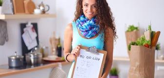 Vrouw in de keuken die thuis, zich dichtbij bureau met omslag bevinden Royalty-vrije Stock Foto's