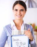 Vrouw in de keuken die thuis, zich dichtbij bureau met omslag bevinden Stock Foto's