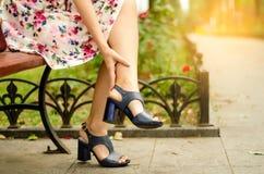 Vrouw in de kleding van de voet in de schoenen van de pijn van de bankstraat in de benen royalty-vrije stock fotografie