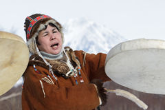 Vrouw in de nationale kleding die van Koryak met tamboerijn en het zingen dansen Stock Afbeelding