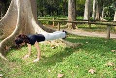 Vrouw in de Positie van de Opdrukoefening naast boom-Horizontaal royalty-vrije stock foto