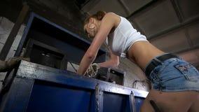 Vrouw in de reparaties van een fabrieksmachine stock videobeelden