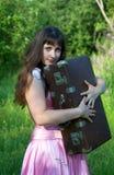 Vrouw in de roze kleding met oude koffer Royalty-vrije Stock Afbeeldingen