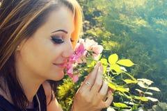Vrouw in de ruikende rozen van de bloemtuin Stock Foto's