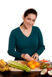 Vrouw in de sinaasappel van de keukenschil stock afbeeldingen
