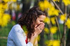 Vrouw de status dicht bij bloemen niest Royalty-vrije Stock Foto
