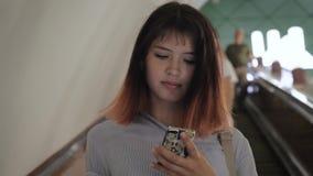 Vrouw de Status op Roltrap daalt naar Ondergrondse Metro Gebruikend Smartphone stock video