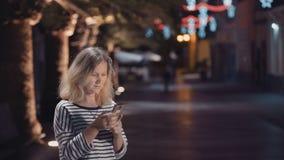 Vrouw in de straat van een nachtstad met een elektronisch apparaat stock videobeelden