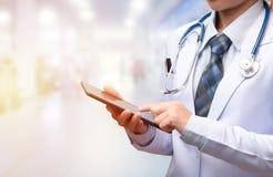 Vrouw de tablet van de artsenholding en het richten van wijsvinger aan het scherm royalty-vrije stock fotografie