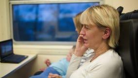 Vrouw in de trein die een telefoonbespreking hebben Moeder en stock footage