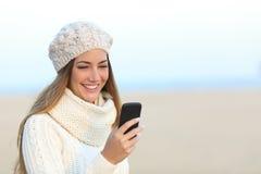 Vrouw in de winter die een slimme telefoon met behulp van Royalty-vrije Stock Afbeeldingen
