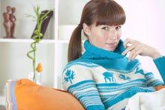 Vrouw in de winterkleren thuis Stock Afbeelding