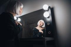 Vrouw in de zitting van de blondepruik dichtbij spiegel in kleedkamer Royalty-vrije Stock Afbeeldingen
