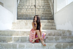 Vrouw in de zitting van de de zomerkleding op de steenstappen Stock Fotografie