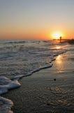 Vrouw in de zonsondergang op het strand Stock Afbeelding