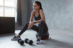 Vrouw in de Zwarte Modieuze Zitting van de Sportenslijtage op Fitness Bal royalty-vrije stock afbeeldingen