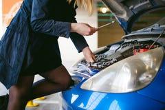Vrouw dichtbij auto` s kap jong blonde in behandeld parkeren van winkelcentrum, tribunes dichtbij auto met opgeheven de bonnet va stock foto