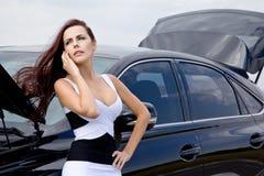 Vrouw dichtbij de gebroken auto Stock Afbeeldingen