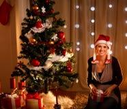 Vrouw dichtbij de holdingsgift van de Kerstboom Stock Afbeelding