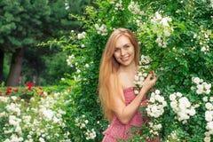 Vrouw dichtbij de rozen royalty-vrije stock afbeeldingen