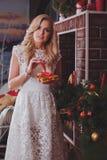 Vrouw dichtbij een nieuw-jaarboom met giften Royalty-vrije Stock Foto's