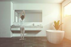 Vrouw dichtbij een tweelinggootsteen in een witte badkamers Royalty-vrije Stock Afbeelding