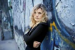 Vrouw dichtbij grungy muur Stock Foto