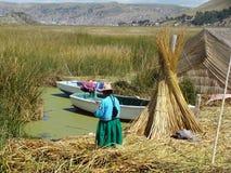 Vrouw dichtbij haar familieboten bij één van de eilanden van Uros - Meer Titicaca Stock Fotografie