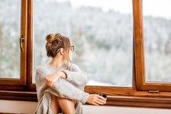 Vrouw dichtbij het venster tijdens de winter stock afbeeldingen