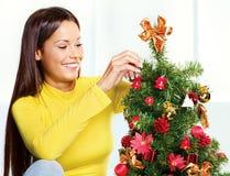 Vrouw dichtbij Kerstmisboom Stock Foto