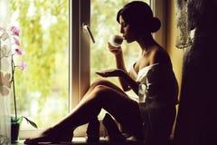 Vrouw dichtbij venster stock foto