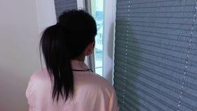 Vrouw dichtbij venster in de ochtend stock footage
