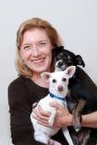 Vrouw die 2 kleine honden houdt Stock Foto's