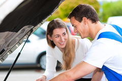 Vrouw die aan autowerktuigkundige spreekt in reparatiewerkplaats Royalty-vrije Stock Foto's