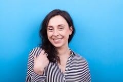 Vrouw die aan de camera op blauwe achtergrond glimlachen stock foto