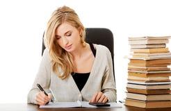 Vrouw die aan examen voorbereidingen treffen, die op calculator tellen Royalty-vrije Stock Foto