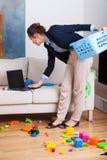 Vrouw die aan haar laptop tijdens het schoonmaken van woonkamer werken Royalty-vrije Stock Foto